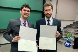 Imagem: Foto de dois homens brancos, de paletó e gravata, segurando placas de homenagem