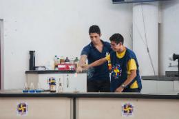 Imagem: foto de dois jovens em um balcão fazendo um experimento químico