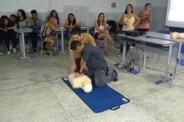 Imagem de instrutor ensinando estudantes a fazer massagem cardiorespiratória em boneco