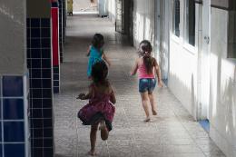 Imagem: Três crianças, de costas, correndo em um corredor (Foto: Viktor Braga/UFC)