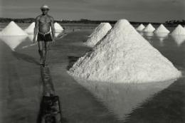 Imagem: Salinas, com um homem caminhando entre as montanhas de sal