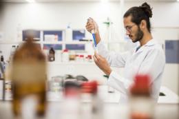 Imagem: foto de um homem de barba vestindo jaleco branco e manipulando itens em um laboratório