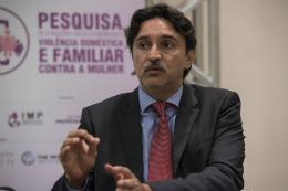 """imagem: homem de terno e gravata, sentado, falando. Ao fundo, banner com a frase """"Pesquisa de Condições Socioeconômicas e Violência Doméstica e Familiar contra a Mulher"""""""