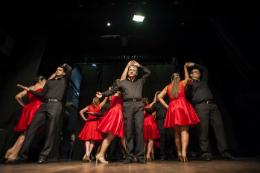 Imagem: foto de servidores dançando no palco do Teatro Universitário