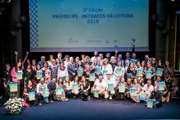 Pessoas com certificados de prêmio reunidas em um palco, sentadas e em pé. Ao fundo, painel escrito 3ª Edição Prêmio IPL - Retratos da Leitura 2018