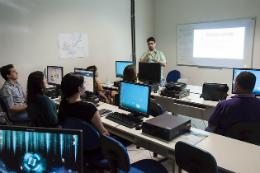 Imagem: foto de servidores em curso da Progep num laboratório de informática e professor à frente