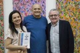 """Imagem: No lançamento do catálogo """"À flor da pele - a pintura visionária de Stênio Burgos"""", o artista está ladeado pela diretora do MAUC, Graciele Siqueira, e pelo reitor Henry Campos (Foto: Ribamar Neto/UFC)"""