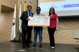 Imagem: foto do estudante vencedor com equipe julgadora segurando um cheque