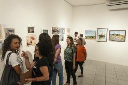 Imagem: Foto de servidores vendo as obras expostas na exposição do ano passado no Museu de Arte da UFC