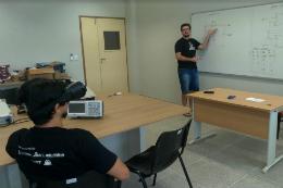 Imagem: Foto de um estudante em sala de aula com óculos adaptado observando a explicação de um professor na lousa