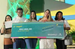 Cinco pessoas em foto posada seguram um cheque com o prêmio do segundo lugar do hackathon