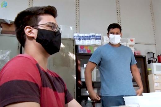 Imagem: Dois estudantes de máscara sendo entrevistados dentro do laboratório