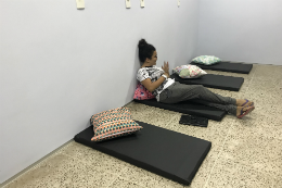 Imagem: foto de uma jovem sentada em um dos colchonetes pretos que estão no chão da sala