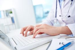 Foto de um médico vestido de jaleco acessando o computador