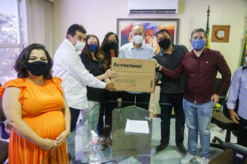 Imagem: Oito pessoas, entre homens e mulheres, segurando uma caixa com um dos equipamentos entregues ao Campus de Crateús (Foto: Divulgação/SECITECE)