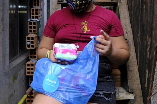 Imagem: foto de uma mulher negra sentada em um banco segurando uma sacola plástica azul e retirando dela um pacote de absorventes descartáveis