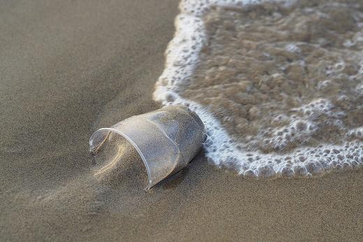 Copo de plástico jogado na areia da praia, com água do mar o molhando